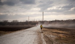 A firefighter walks to a tanker truck. Burnt fields can be seen on both sides of the road.